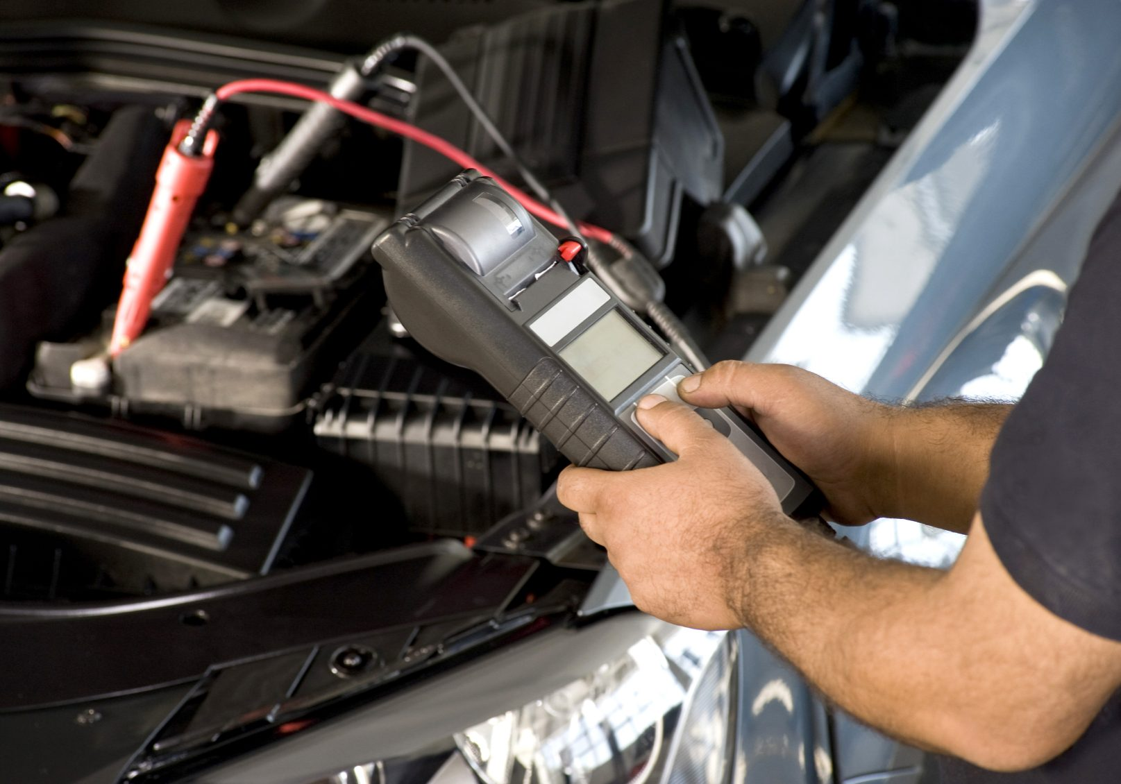 Image of a mechanic holding a diganostic tool to help with car battery testing