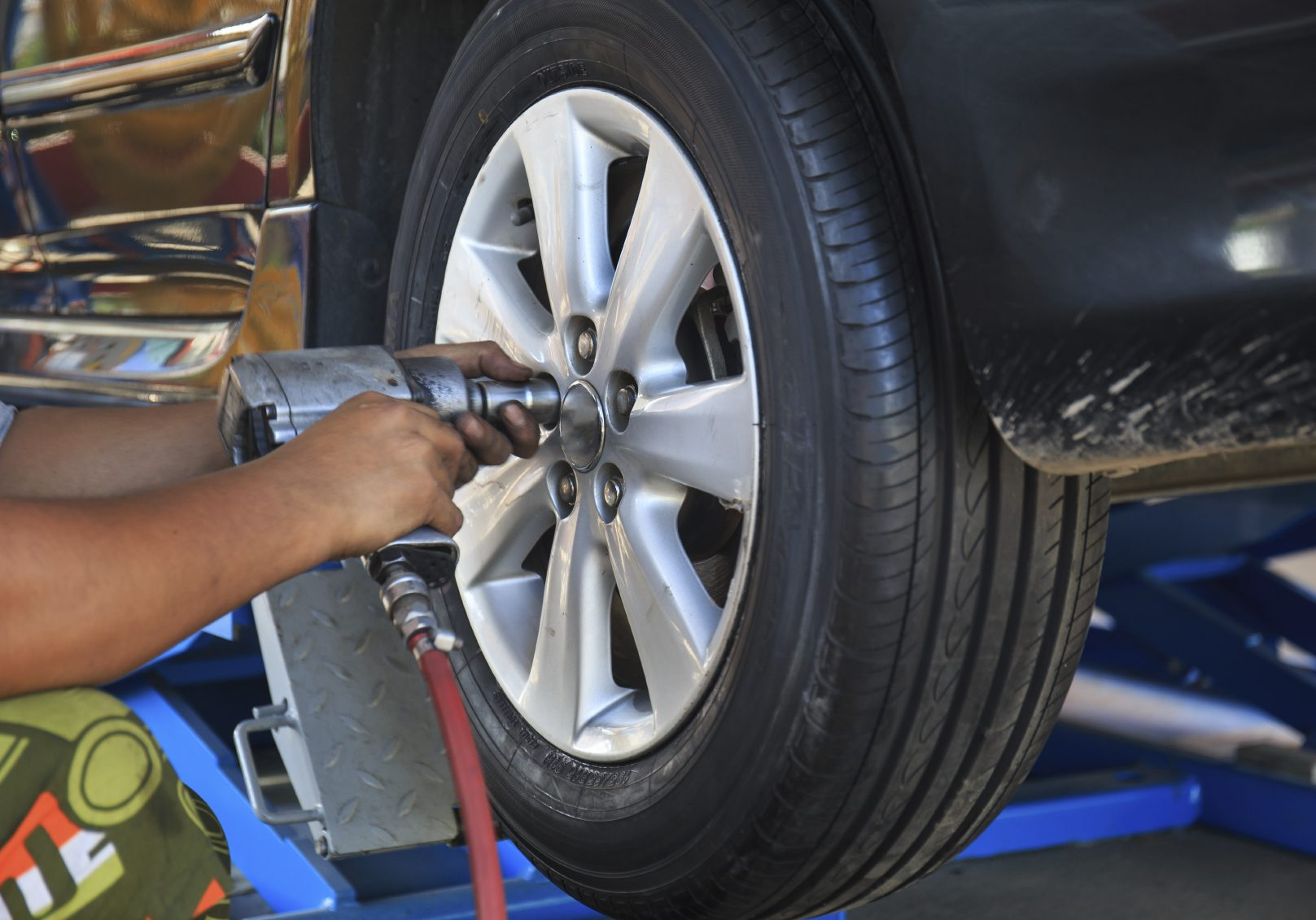 Image of a tire being removed in preparation for a wheel alignment